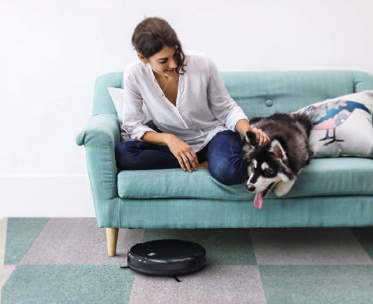 A person sits on their sofa with a dog while the vacuum moves on the floor