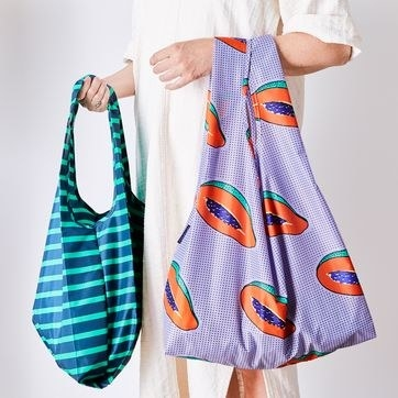person holding a stripe bag and a purple fruit print bag