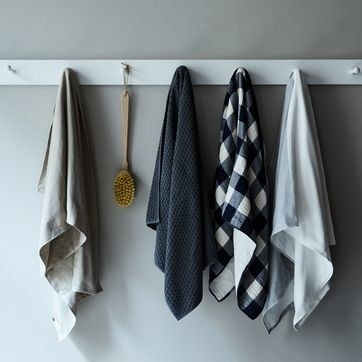towels in a neutral color palette hanging up on a row of wall pegs