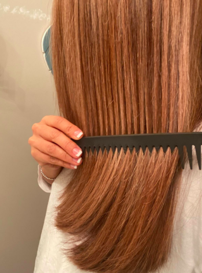 Reviewer uses detangling comb to work out knots in their reddish brown hair