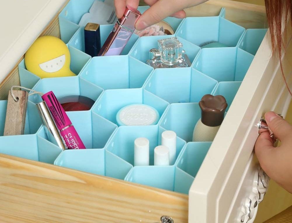A person neatly placing makeup and grooming products in the organiser.