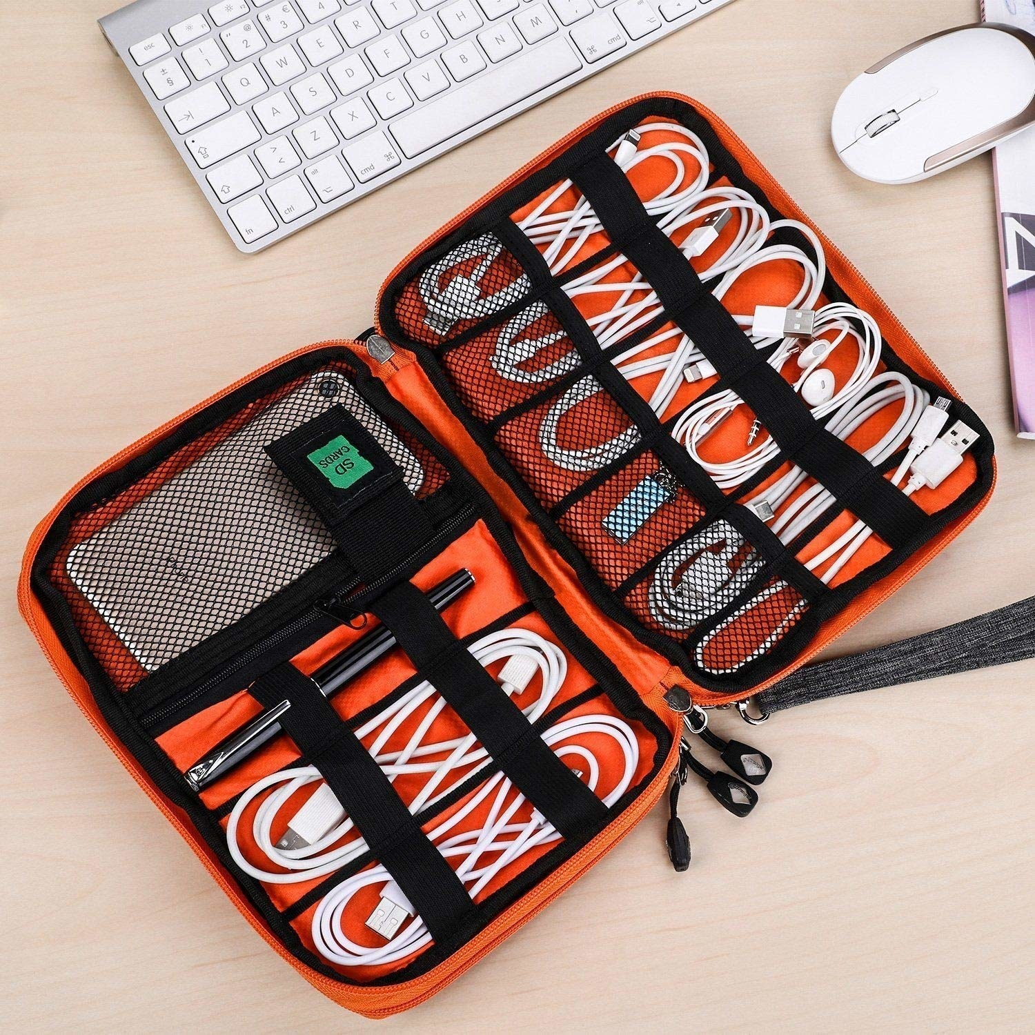 Cables, earphones, a phone, and a pen stored in the orange and black organiser.