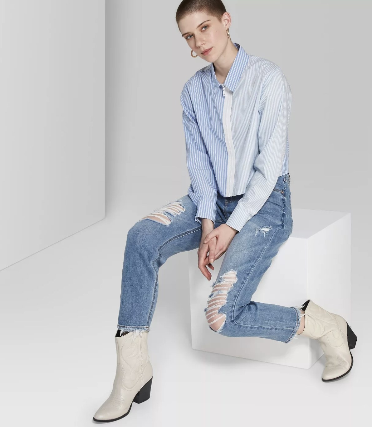 Model in the ripped, light wash, straight-legged jeans