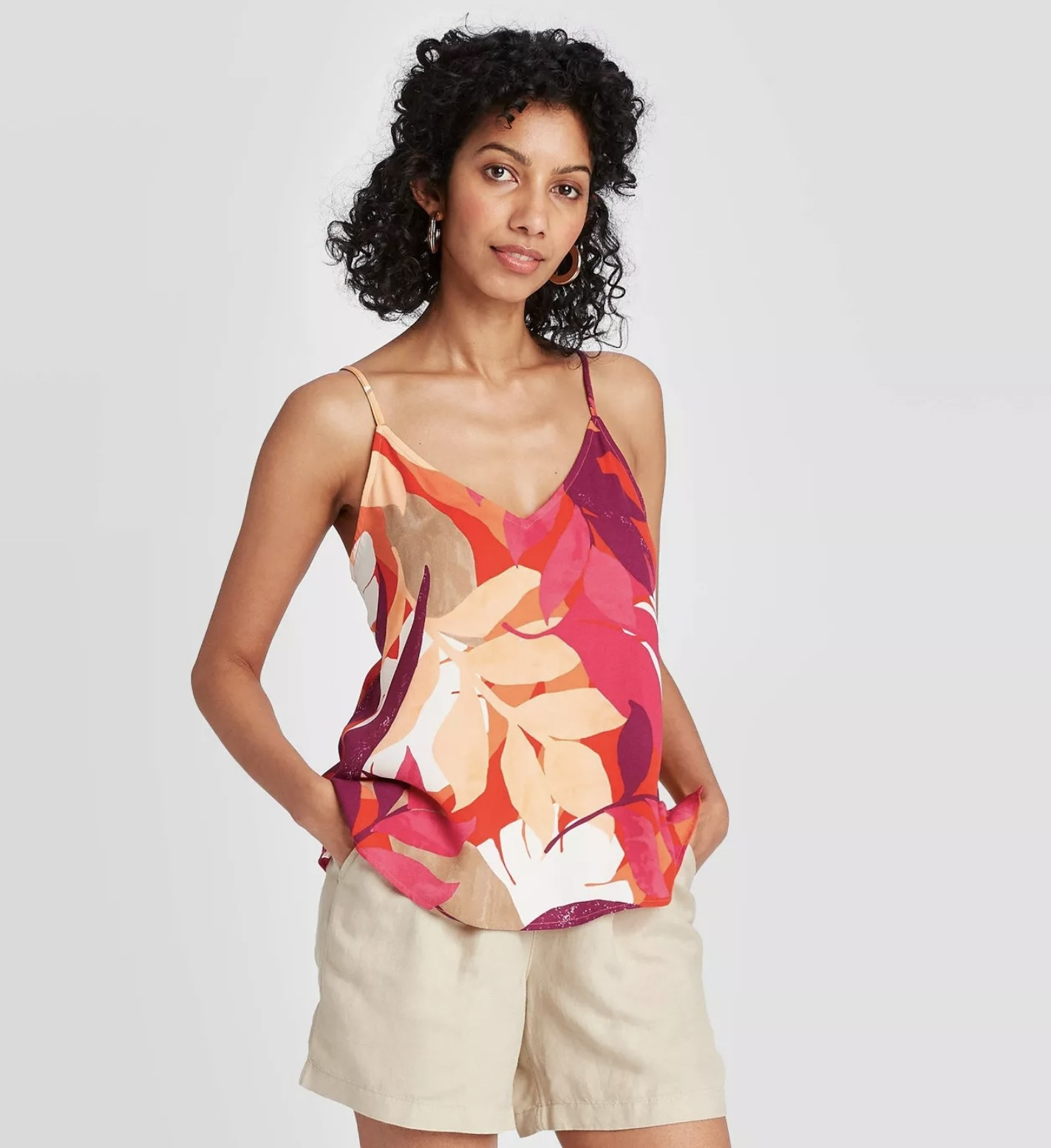 Model wearing the leaf-patterned, orange and pink, spaghetti strap tank