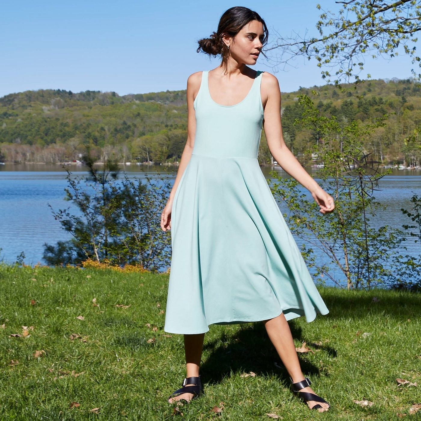 A model in a scoop neck pale blue dress that falls below the knee