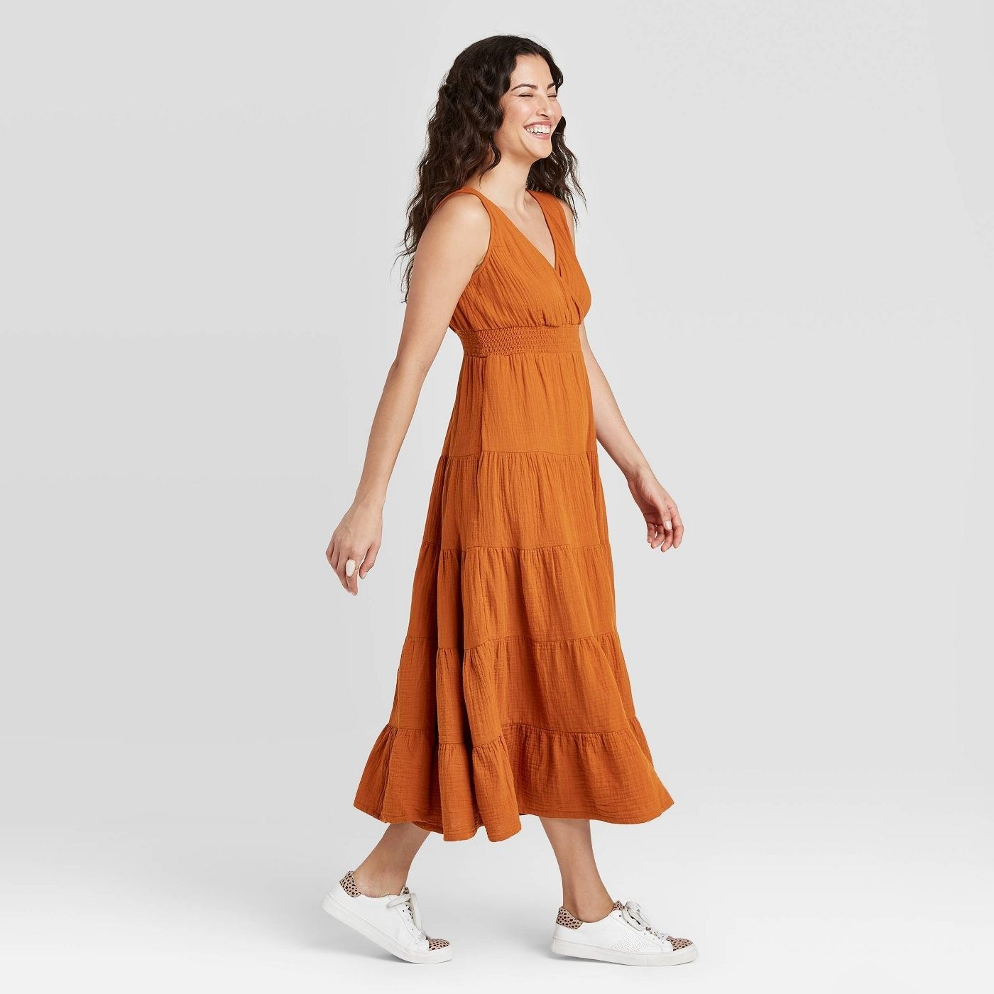 A model in an orange sleeveless V-neck maxi dress