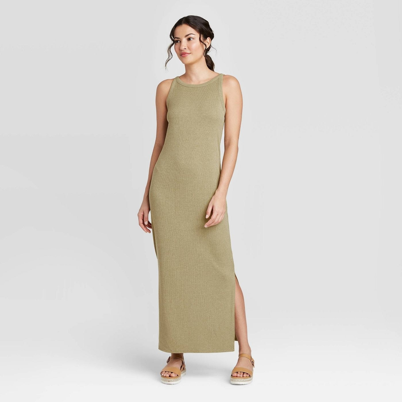 A model in a pale green sleeveless dress with slits at the hem