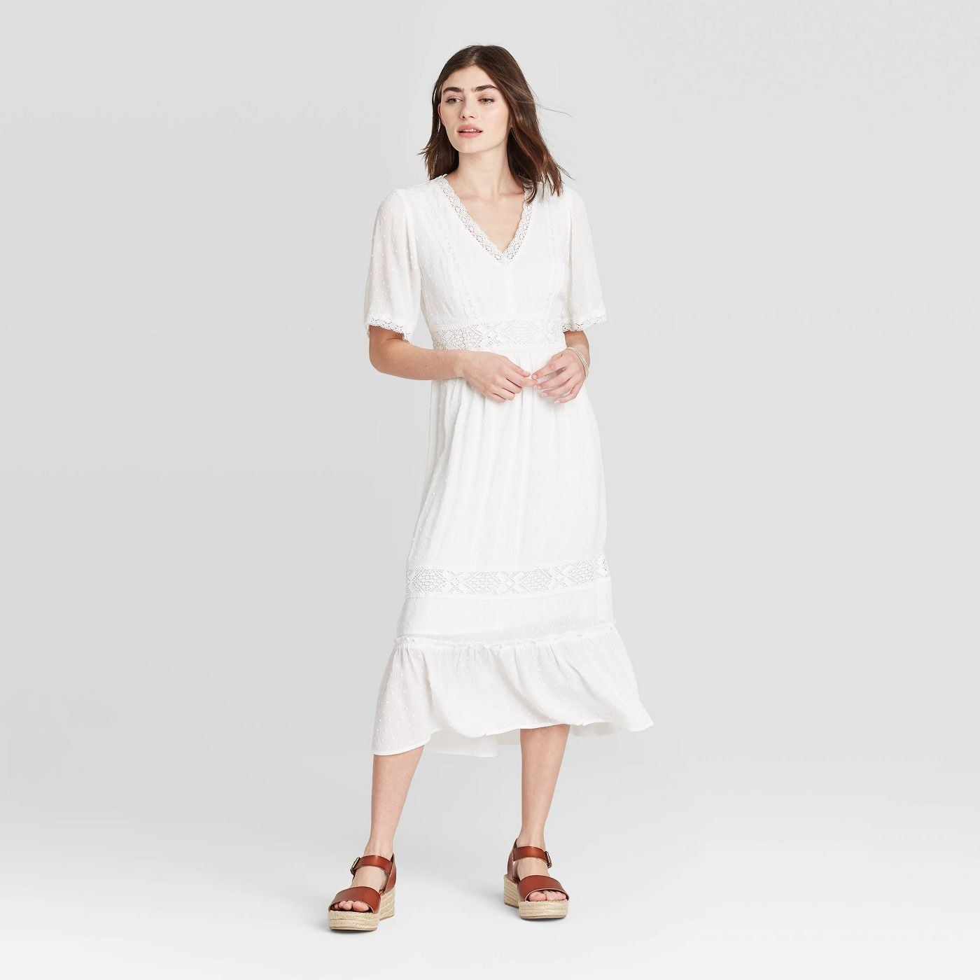 A model in a midi length dress with a short sleeve and V-neckline