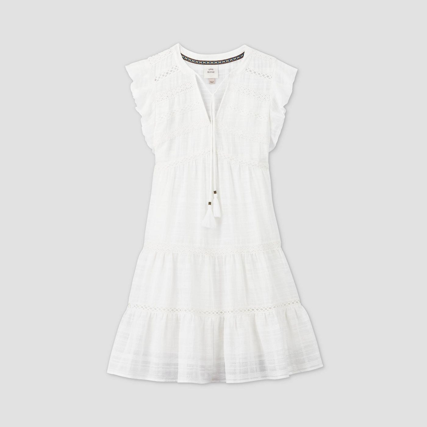 A white tiered eyelet dress with tassel ties at the collar