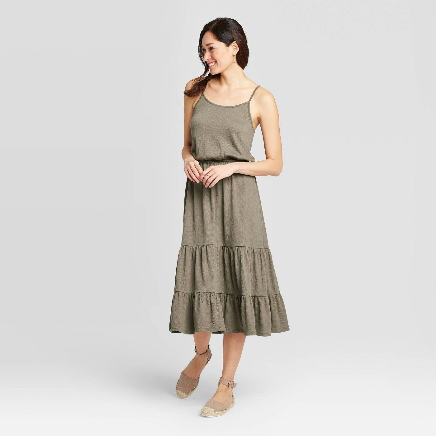 A model in a tiered olive green maxi dress