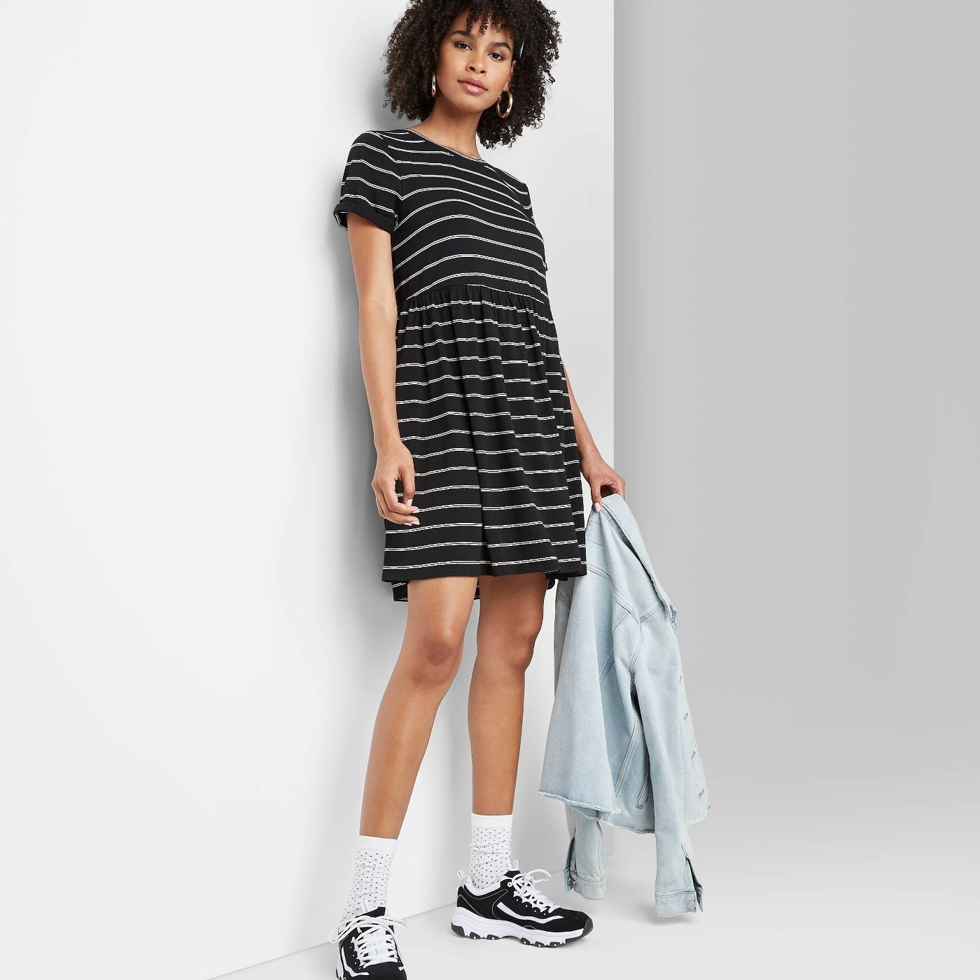 A model in a short-sleeved black and white striped dress that falls above the knee