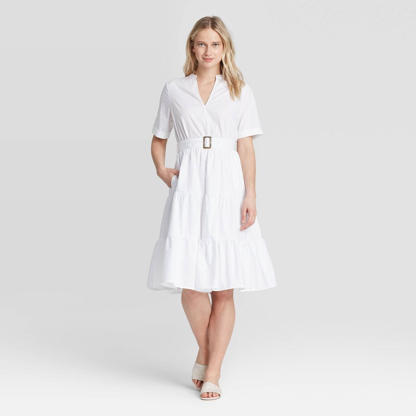 A model in a tiered white knee-length dress with a V-neckline