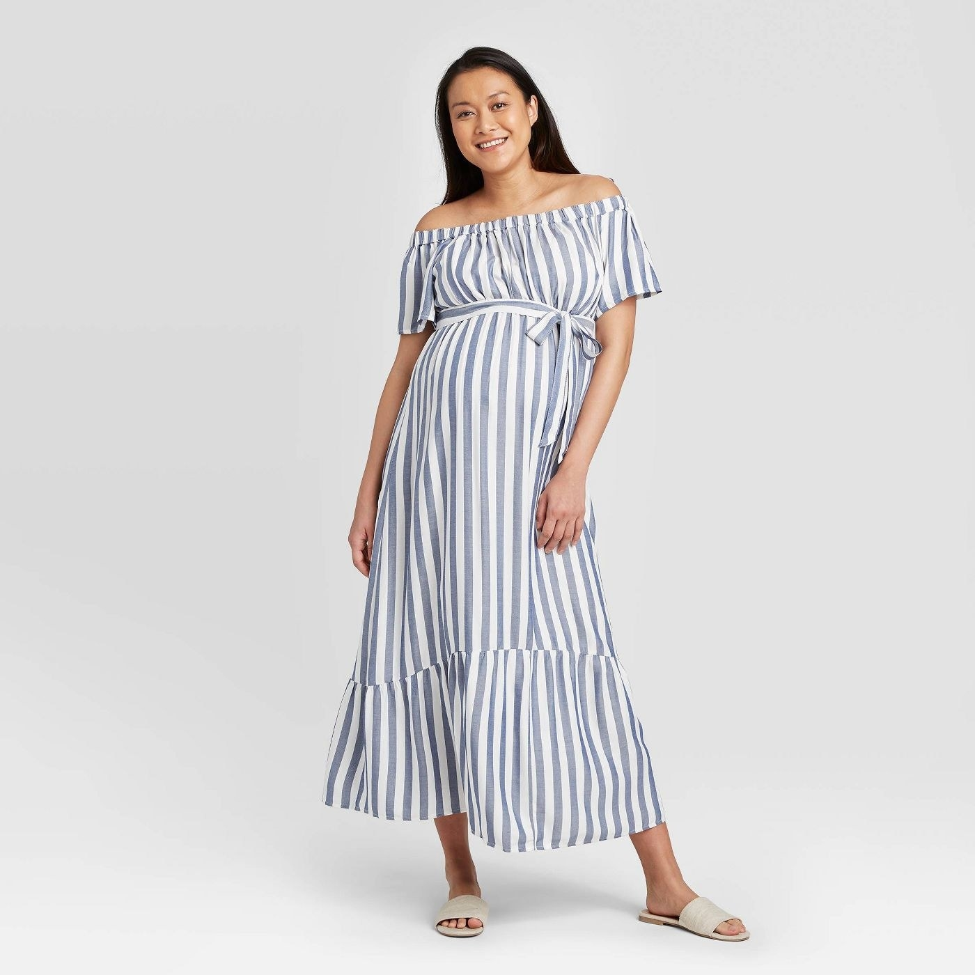 A model in a blue and white horizontally striped dress that falls at the ankle
