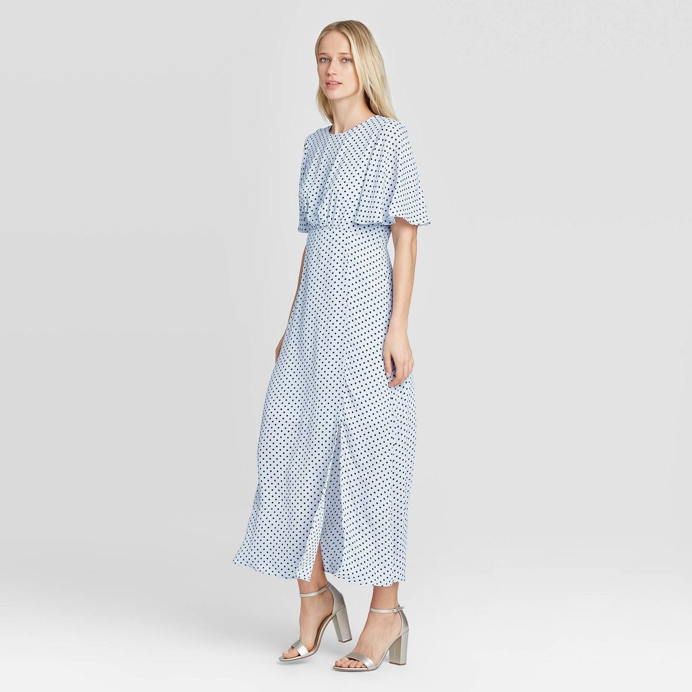 A white blue polka-dotted dress with a high neckline, fluttering sleeves, and a cinch above the waist