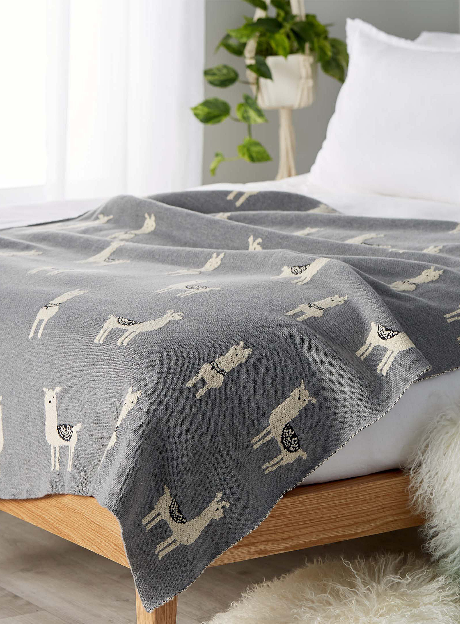 A throw with llamas on it is spread over a bed