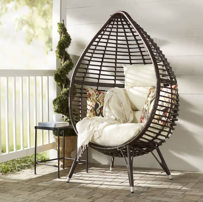 the wicker teardrop chair with pillows
