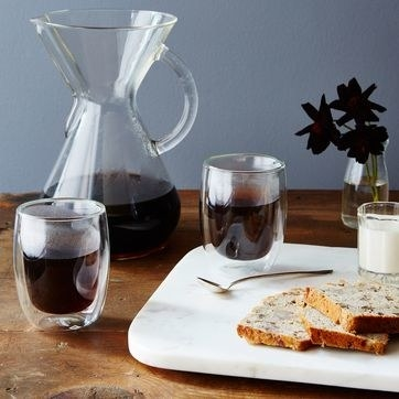 table setting with two cups and a pitcher with the visible juice inside