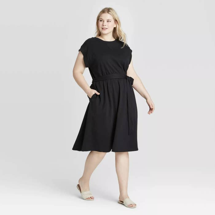 Model wearing a black dress that hits below the knee and covers upper arms