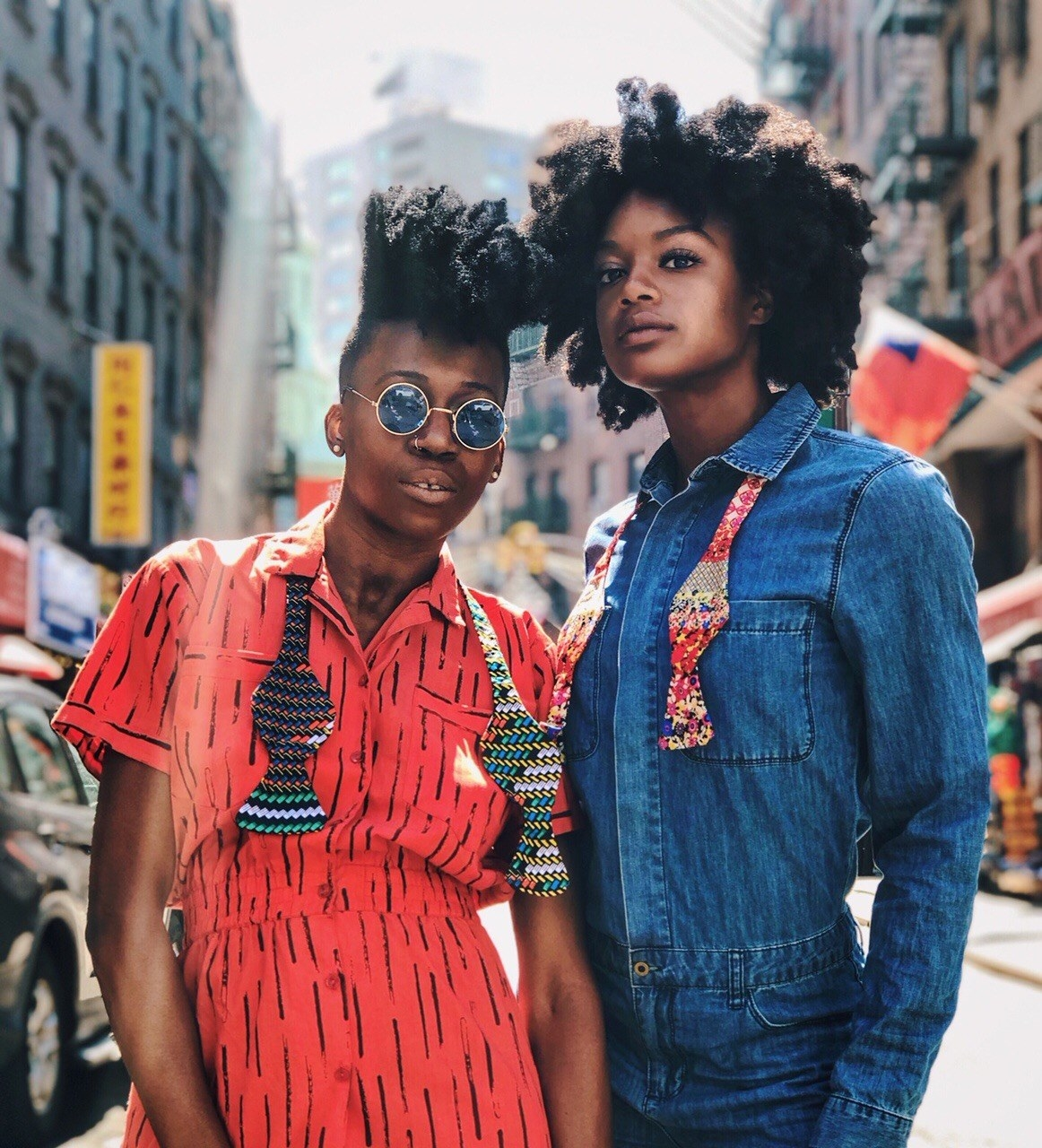Two models wearing colorful, printed neck straps