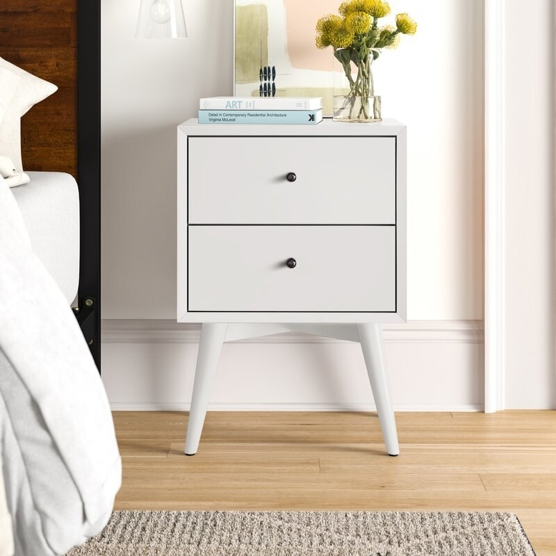 The white nightstand with two drawers and splayed legs