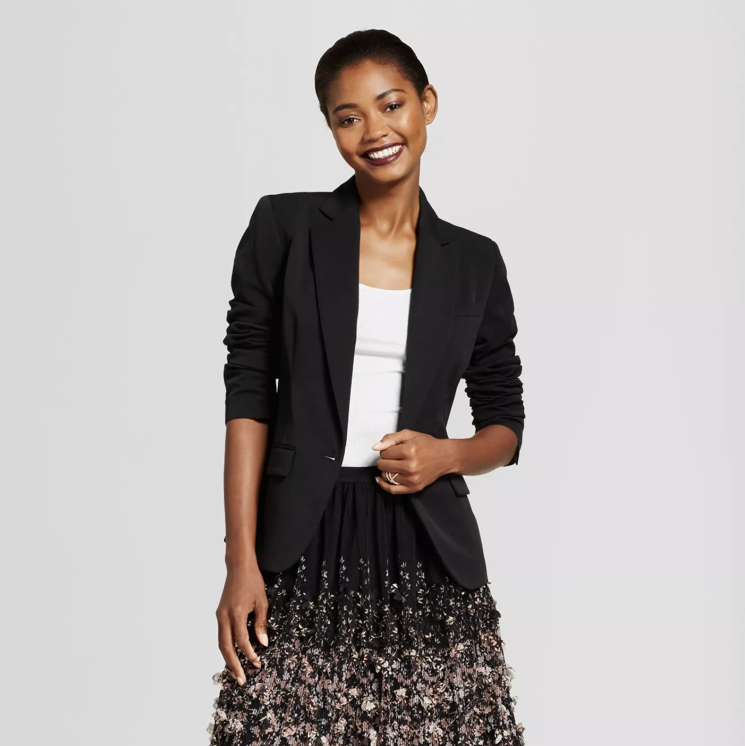 A model wearing a black blazer with the sleeves pushed up to the elbows