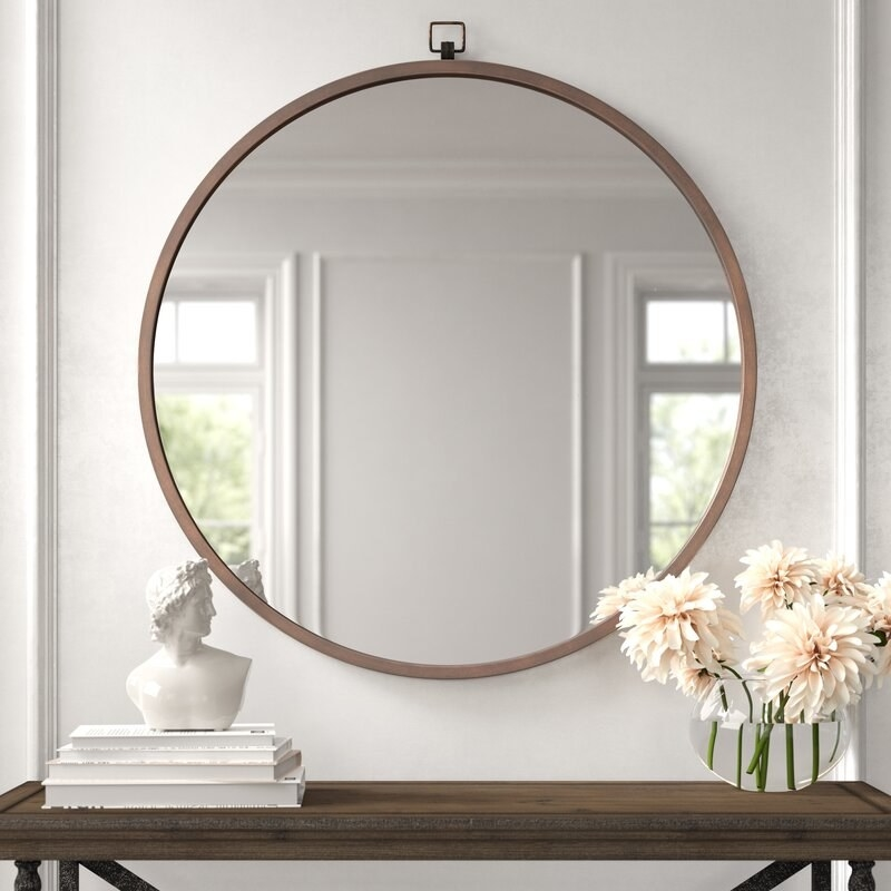The large circular mirror with a bronze cast-iron frame