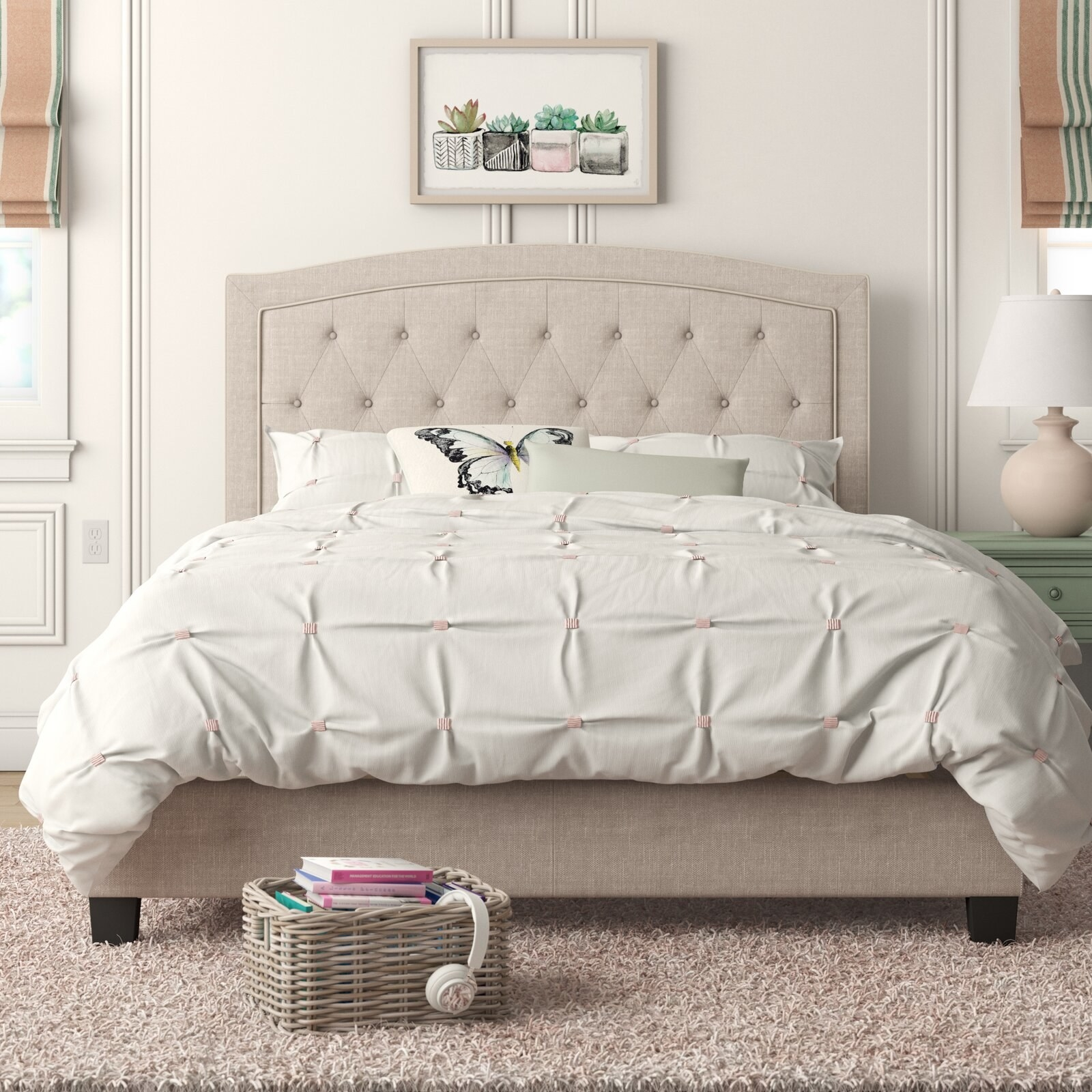The cream colored linen bed with a tufted headboard