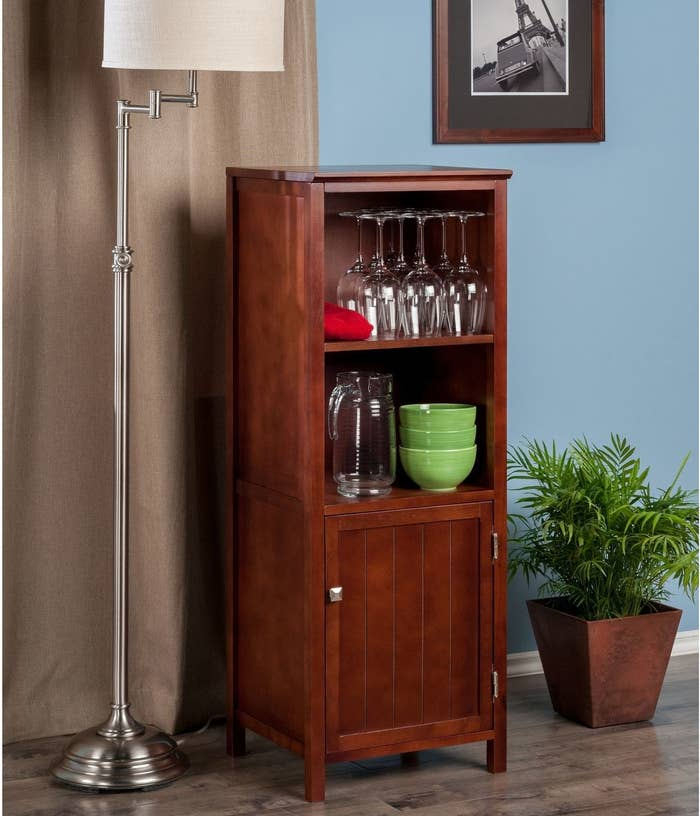 a tall brown wooden cabinet with two shelves and a closed cabinet closes to the base