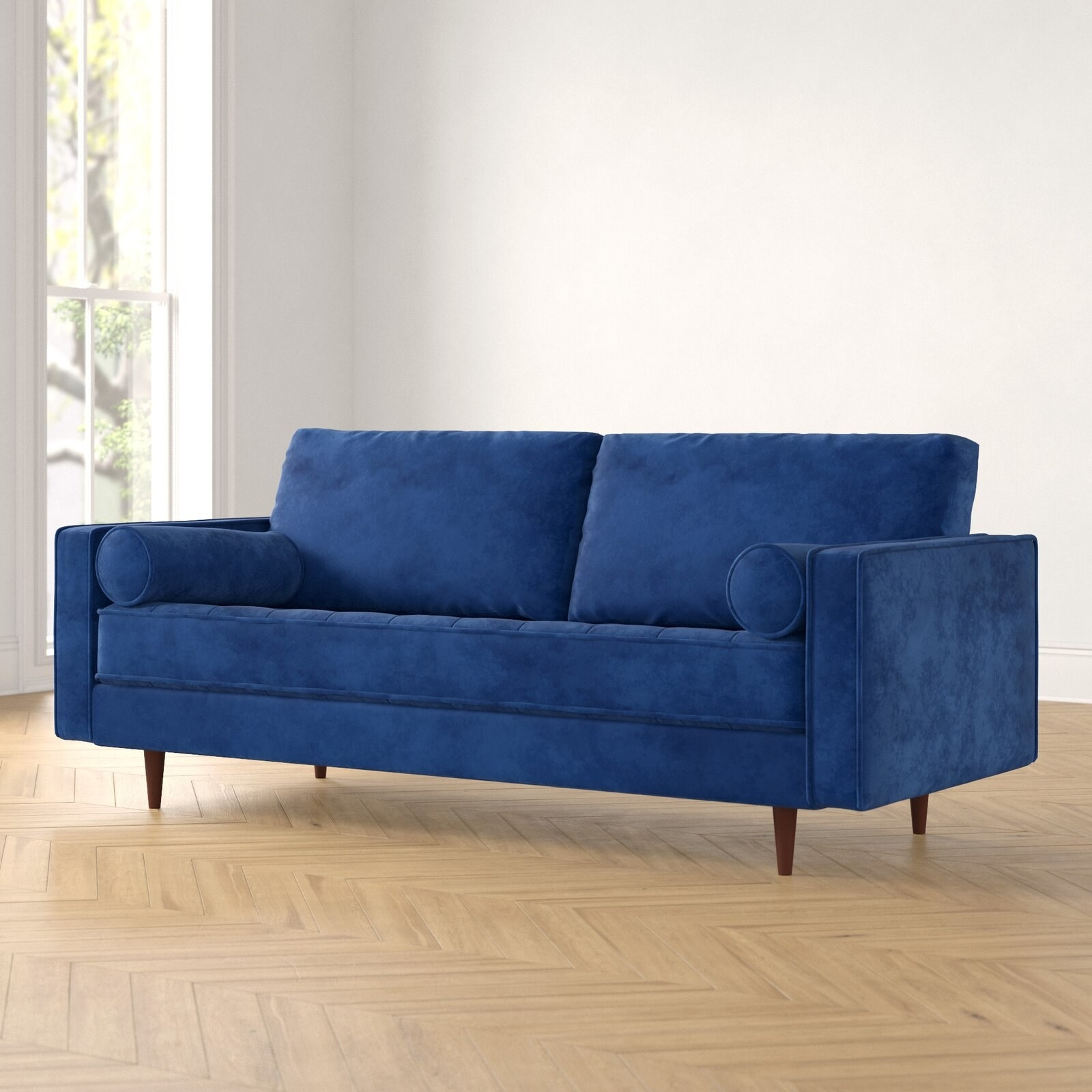 The blue velvet square sofa with matching pillows