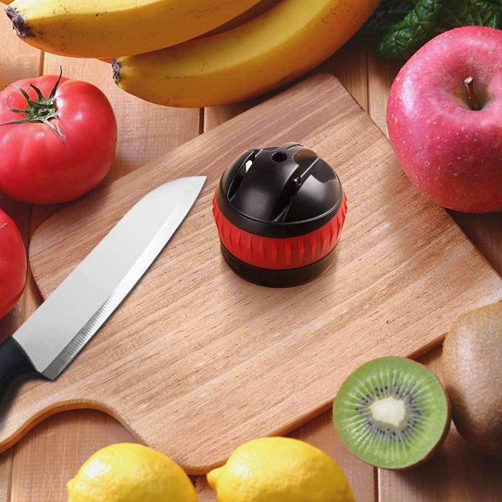 A knife sharpener and a knife are on a cutting board surrounded by produce