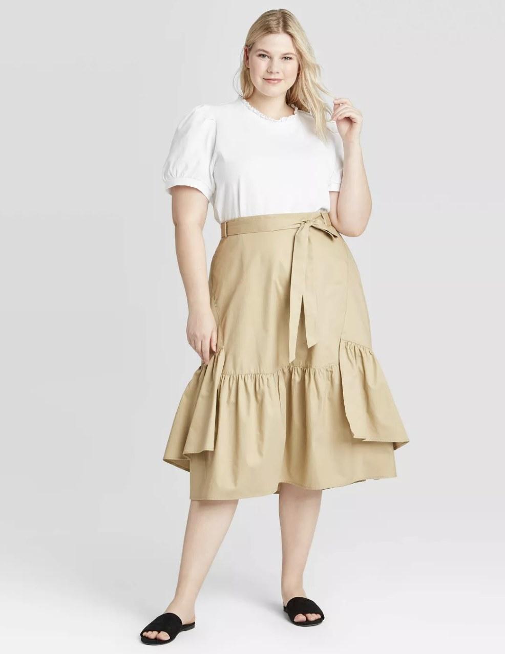 Model wearing the tan midi skirt with a ruffle hem