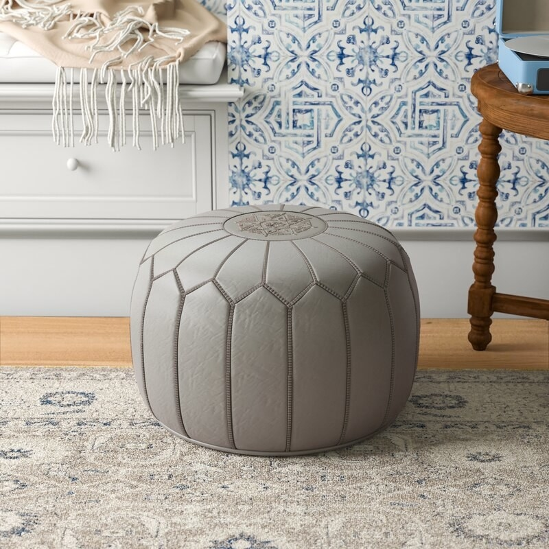 The tufted leather pouf in grey