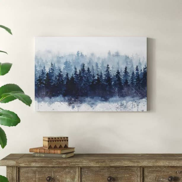 "An ""Indigo Forest"" art print with blue trees and fog hanging above a wooden dresser"