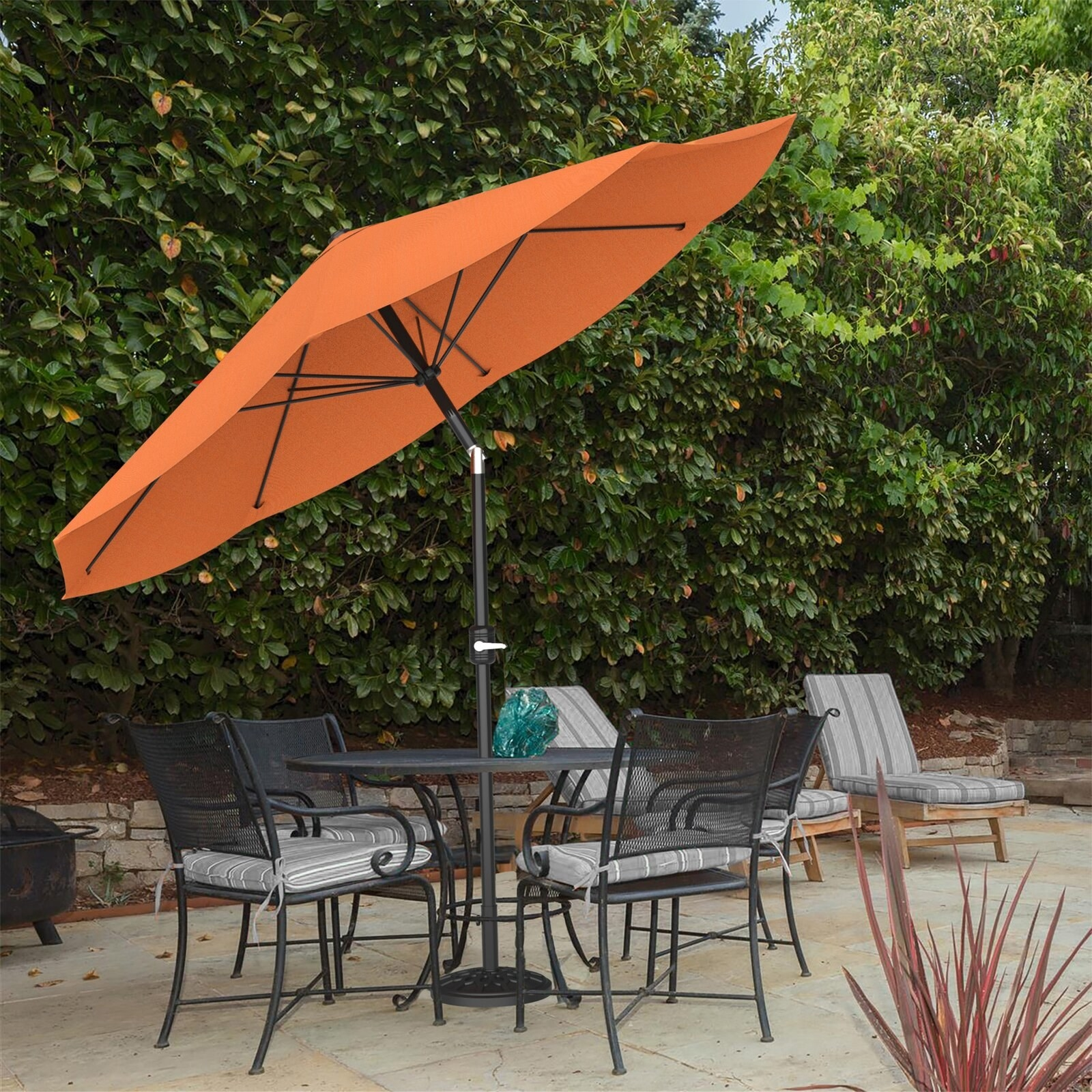 The adjustable umbrella attached to an outdoor dining table