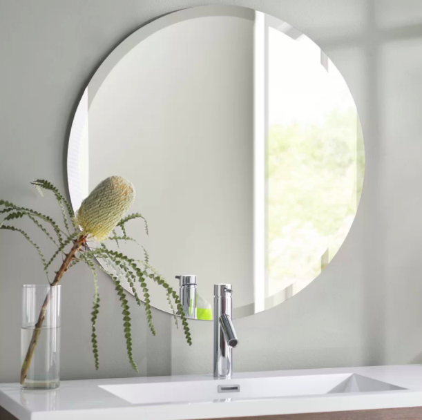 A circular mirror hanging above a white sink in a bathroom