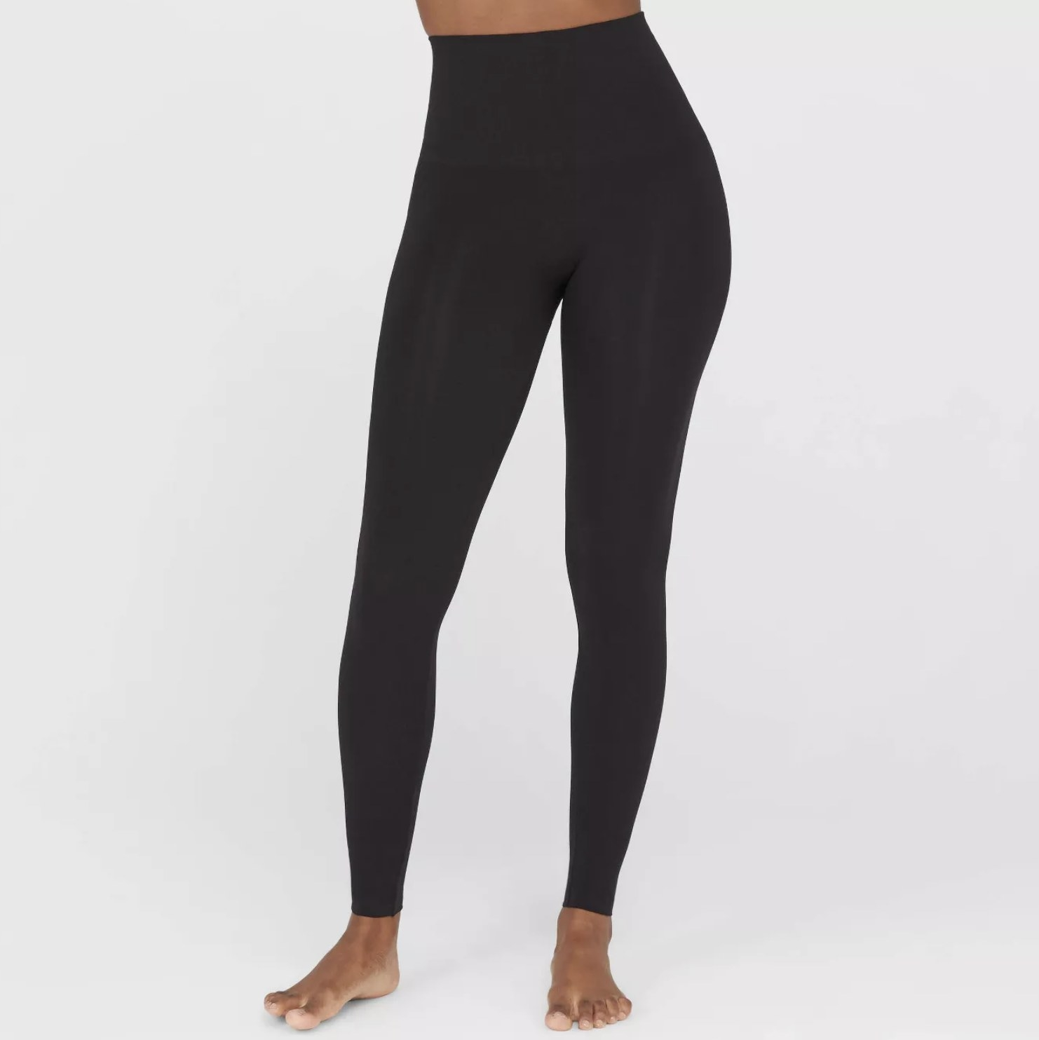 A model wearing a pair of black high-waisted leggings that hit at the ankle
