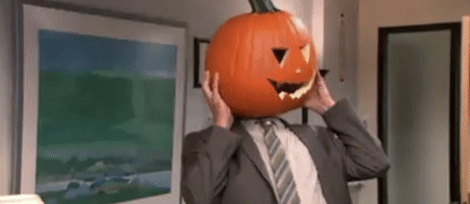 Dwight Schrute from The Office is wearing a gray suit with a white shirt and gray striped tie. On his head is a jack-o-lantern and he is struggling to get it off.