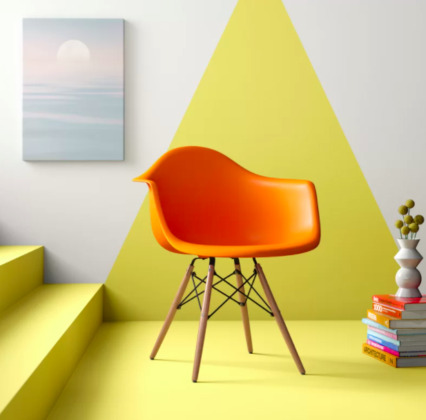 An orange arm chair nestled in between yellow stairs and a cozy pile of books