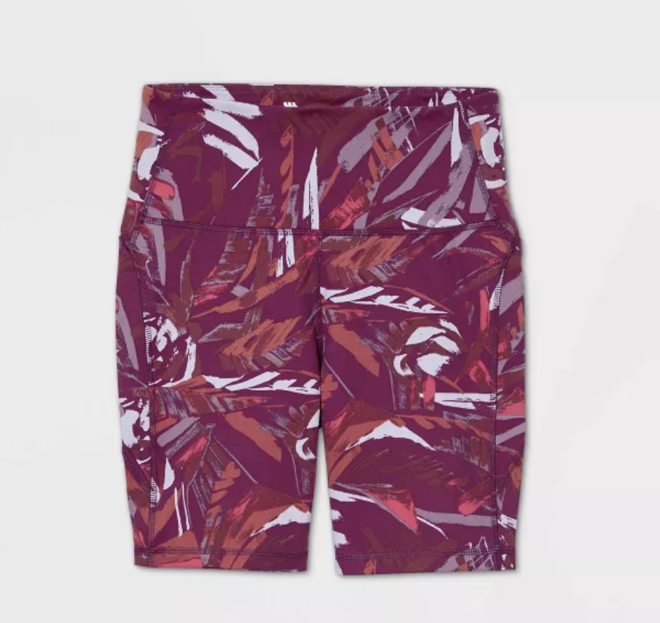 A pair of deep pink elastic bike shorts with burnt orange and pink and white patterns