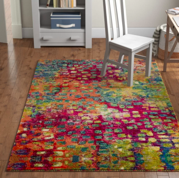 A colorful rectangle rug with blue, red, orange, green, and yellow shades in a home office