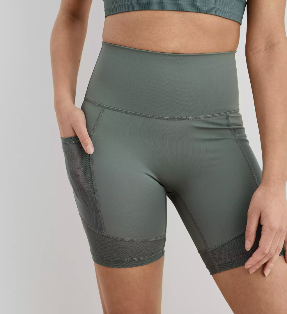 A model in olive green biker shorts with mesh pockets on the sides