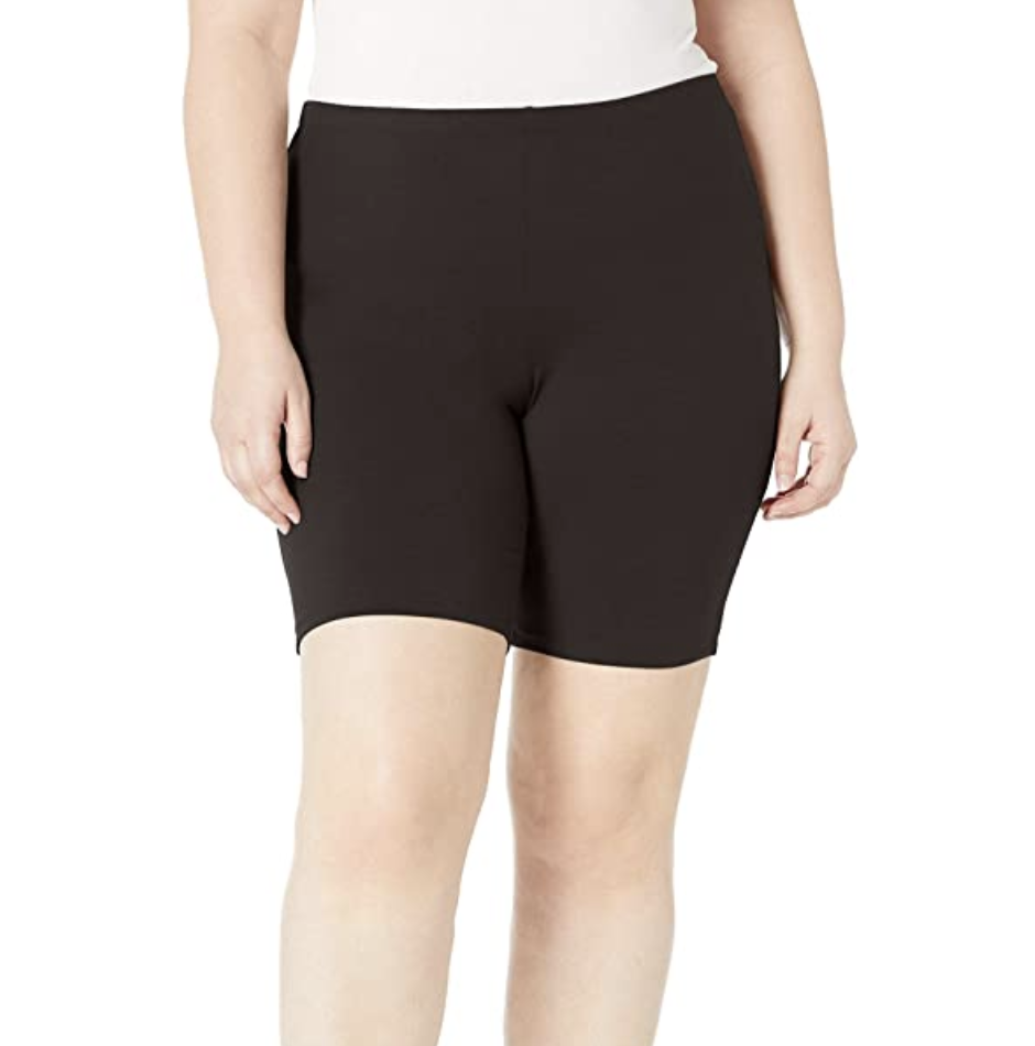 A model in black high waist bike shorts that fall just above the knee