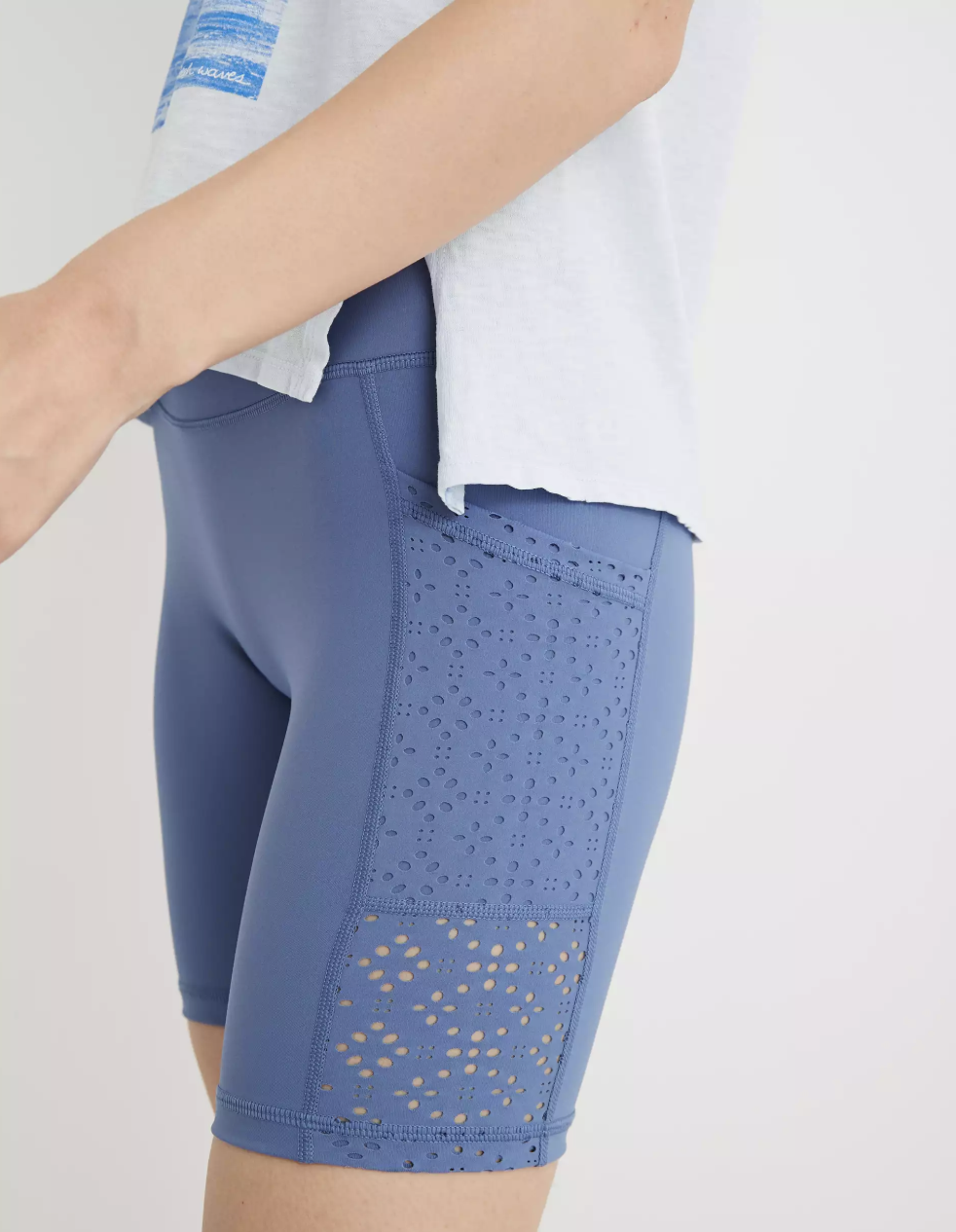 A model in pale blue bike shorts with laser cut detailing on the side pockets