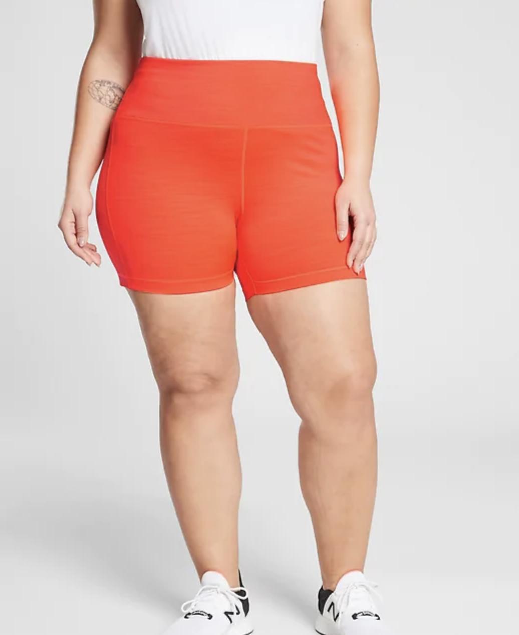 A model in orange high waist bike shorts that fall mid-thigh