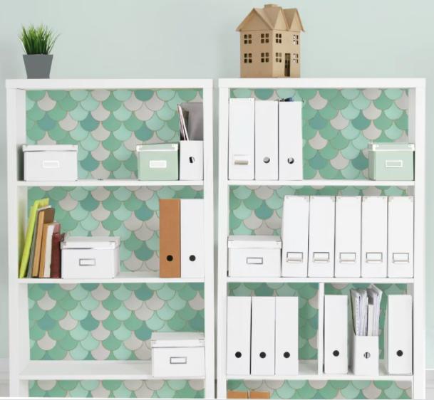 Green and white mermaid-print shelf liner inside a white bookshelf