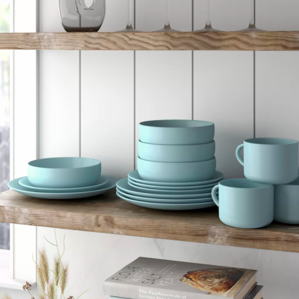 A blue 16-piece dinnerware set with bowls, plates, and mugs on a wood shelf