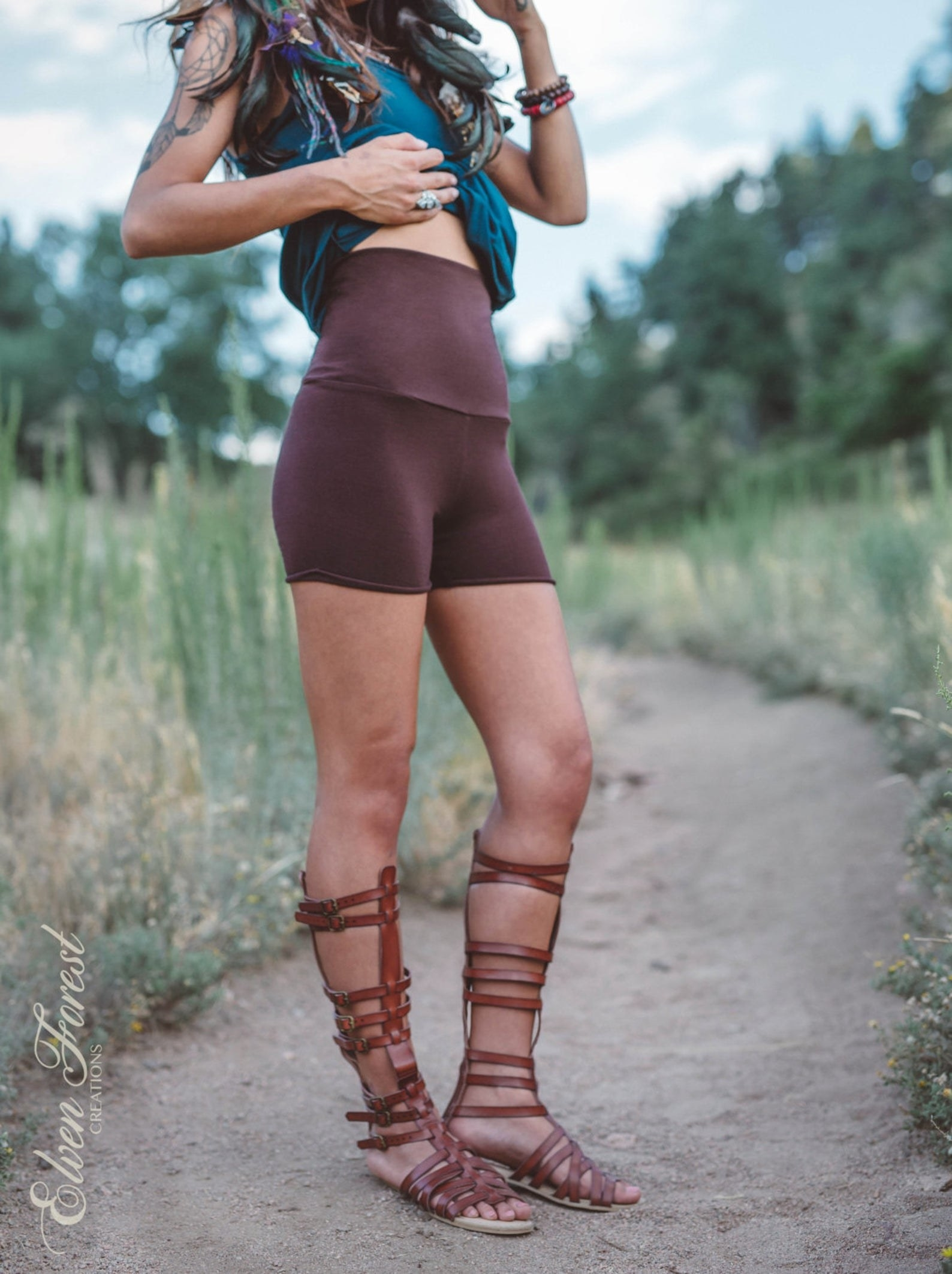 A model in brown high-waisted bike shirts that fall upper mid-thigh