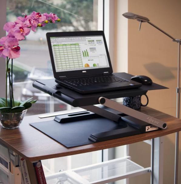 A black adjustable standing desk converter on top of a bookshelf