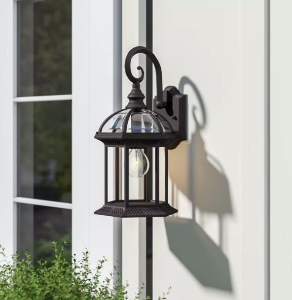 Black outdoor wall lantern placed on the side of a white house