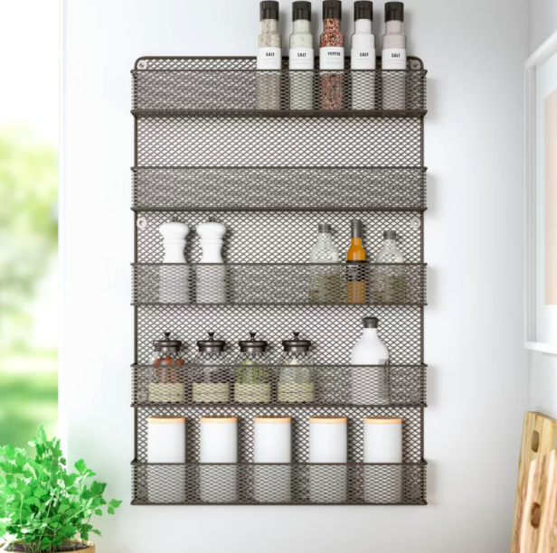 A five-shelf spice rack organizer with spices, oils, and jars in a kitchen